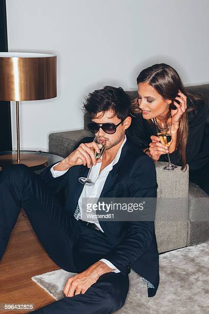 Stylish young couple with glasses of champagne at sofa