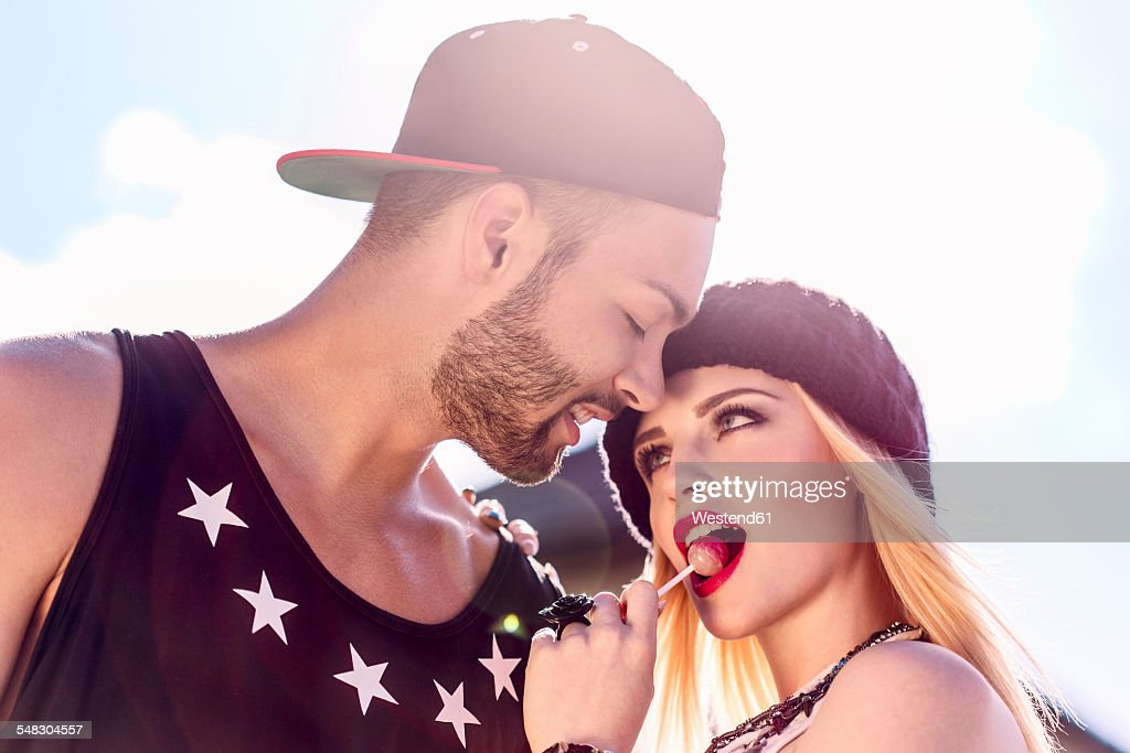 Stylish young couple with lollipop