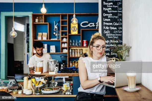 Stylish Young Entrepreneur Working Over Lunch At Cafe