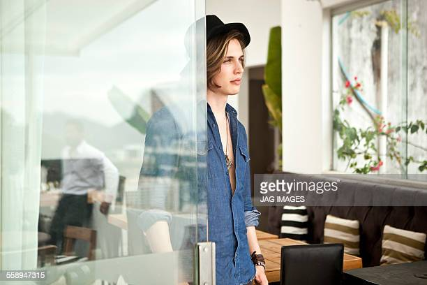 Stylish young man looking out from hotel lobby