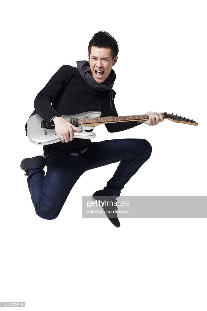 Stylish young man playing guitar