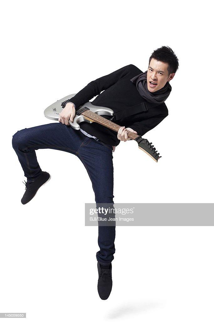 Stylish young man playing guitar : Stock Photo