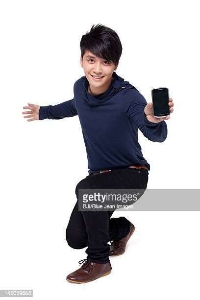 Stylish young man showing mobile phone