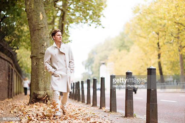Stylish young man strolling through autumn leaves in city park
