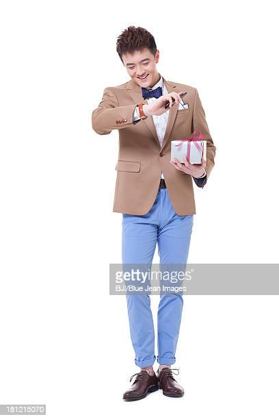 Stylish young man with gift checking the time