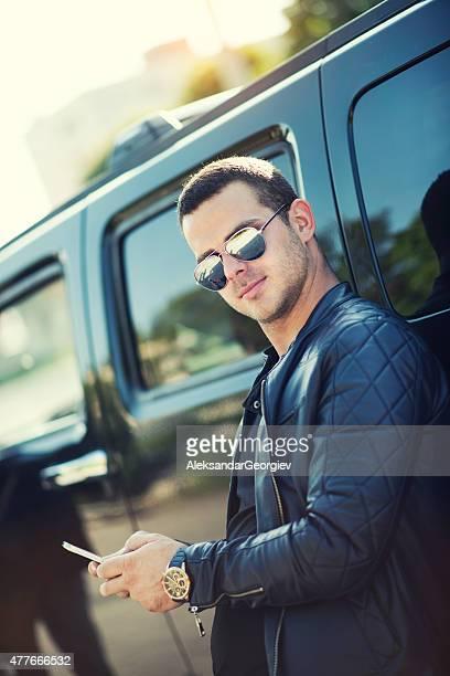 Élégant jeune homme avec des lunettes de soleil Comment envoyer des SMS sur le téléphone intelligent