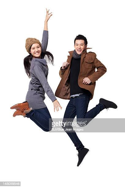 Stylish young people jumping in mid-air