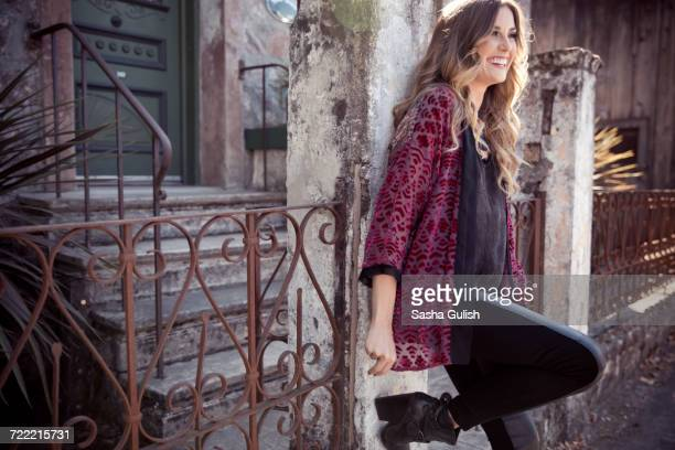 Stylish young woman leaning against front gateway