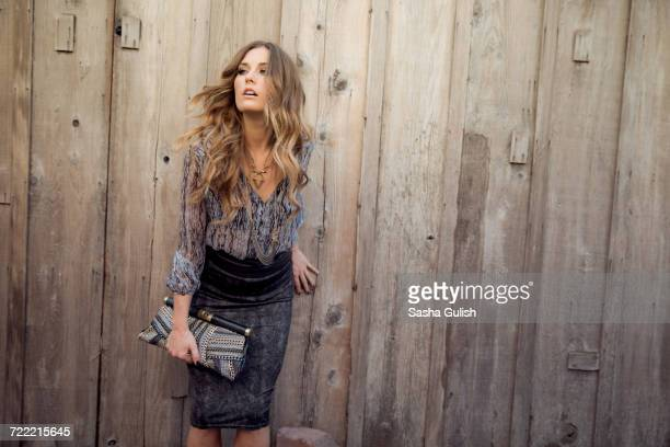 Stylish young woman leaning against wooden door