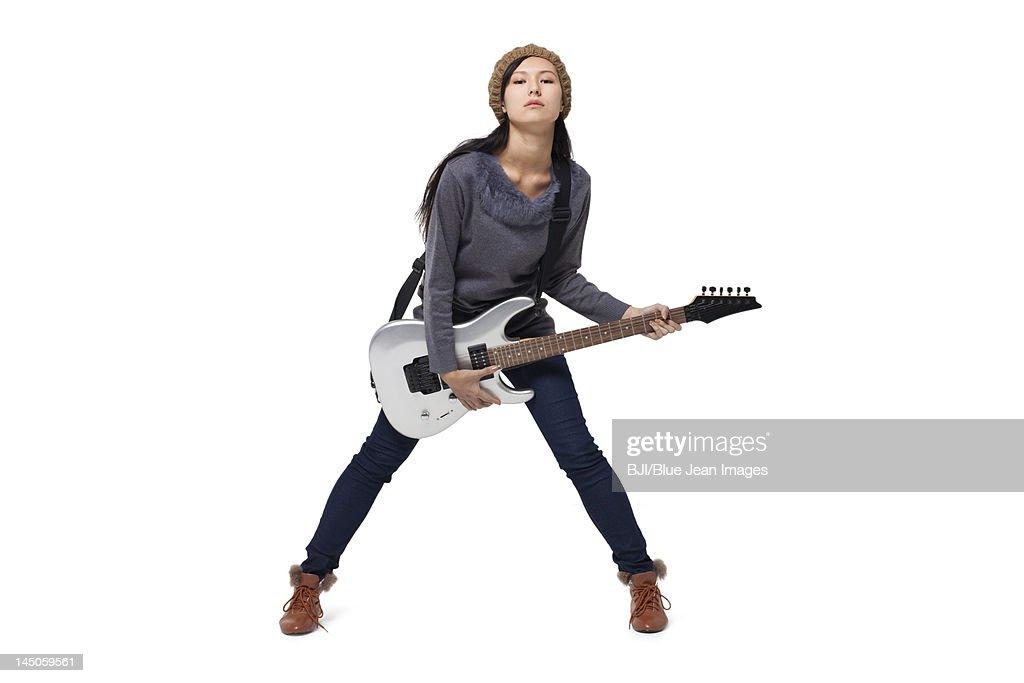Stylish young woman playing guitar