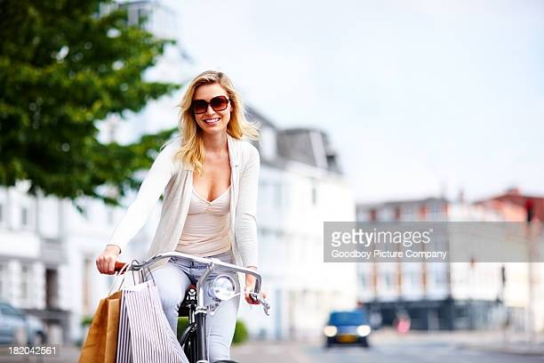 Stylish young woman riding her bicycle on street - Copyspace