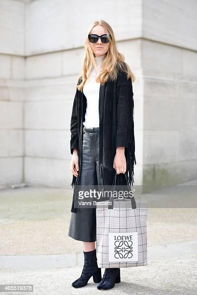 Stylist Alexandra Carl poses wearing an X of Copenhagen coat Acne Studios pants Margiela shoes and Loewe bag on Day 5 of Paris Fashion Week...