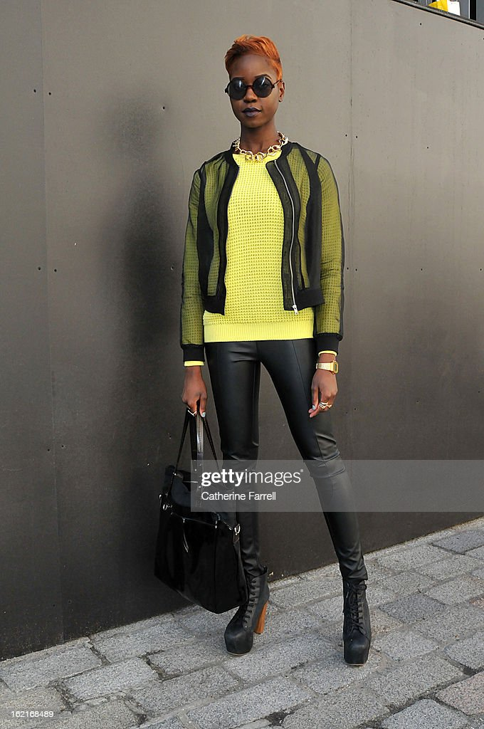 Stylist and blogger Olivia Akot wears an organza style bomber jacket, with neon yellow top from Topshop,accessorised with Go Go Philips necklace, Topshop sunglasses,and Jeffrey Campbell boots from Festival Shoes in Brick Lane during London Fashion Week Fall/Winter 2013/14 on February 19, 2013 in London, England.