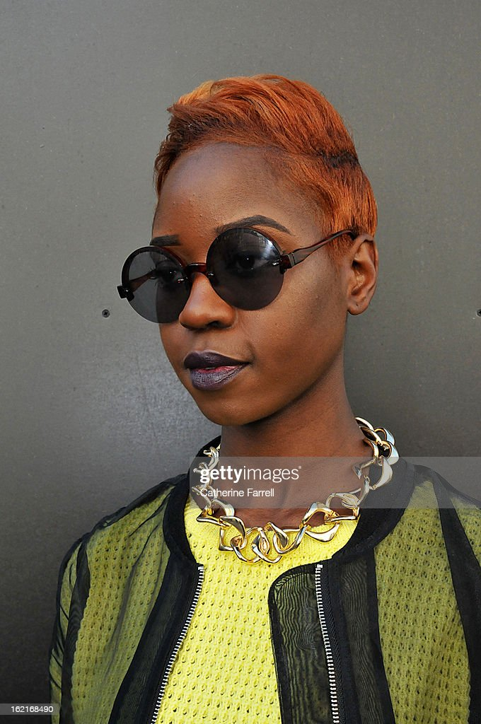 Stylist and Blogger Olivia Akot wears an organza style bomber jacket, with neon yellow top from Topshop,accessorised with Go Go Philips necklace, Topshop sunglasses, and vintage trousers during London Fashion Week Fall/Winter 2013/14 on February 19, 2013 in London, England.