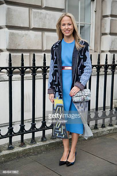 Stylist and fashion blogger Diana Gavrilina wears a Peter Pilotto coat Roksanda Illinic dress Chanel bag and Dior shoes on February 24 2015 in London...
