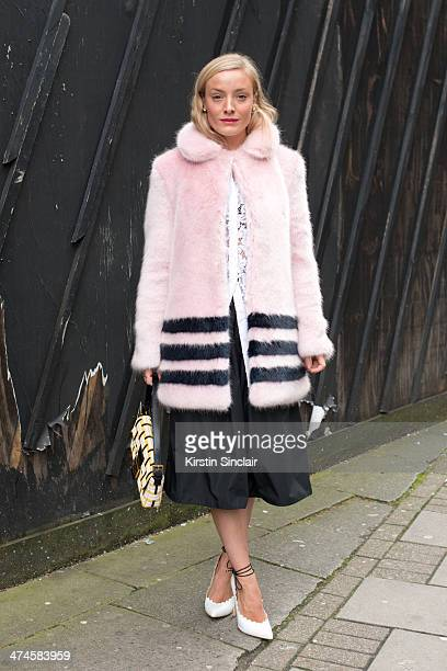 Stylist and Model Kate Foley wears a Shrimp coat Fendi bag Burberry top and skirt on day 4 of London Collections Women on February 17 2014 in London...