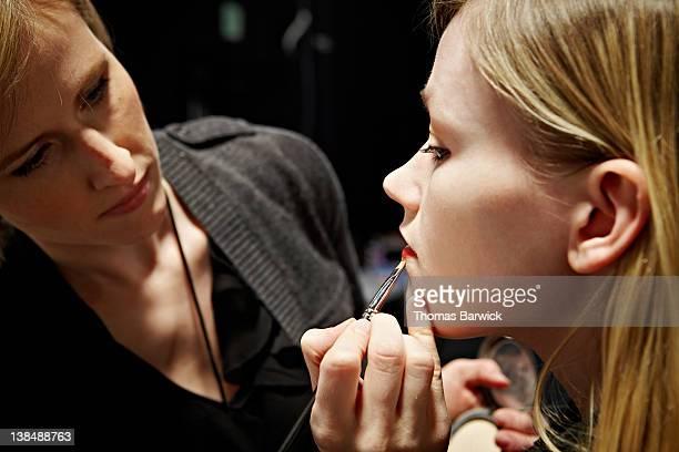 Stylist applying make-up to fashion model