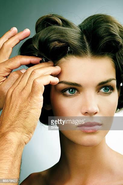 Stylist fixing woman's curls