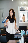 Stylist holding blow dryer in salon