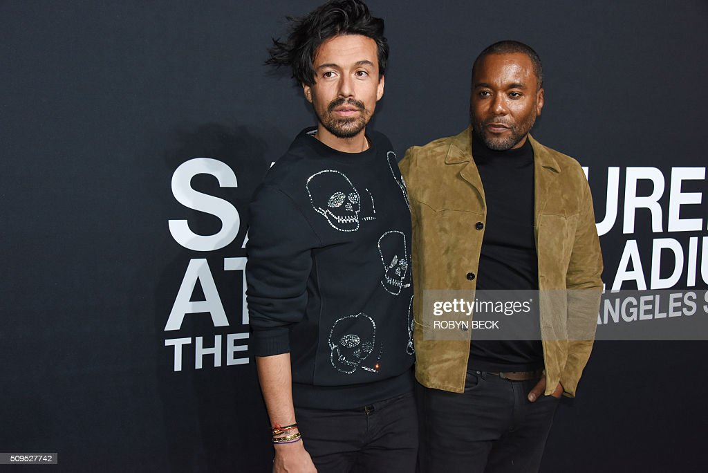 Stylist Jahil Fisher (L) and director/producer Lee Daniels attend the Saint Laurent men's fall line and the first part of its women's collection fashion show at the Paladium, in Hollywood, California, February 10, 2016. / AFP / ROBYN BECK