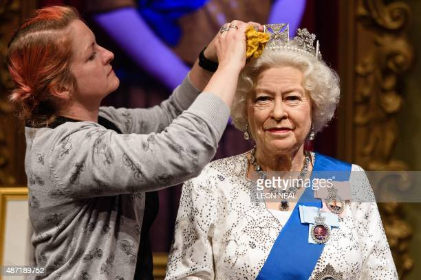 Stylist Jane Anderson poses with the restyled wax figure of Britain's Queen Elizabeth II during a photocall at Madame Tussauds in central London on...