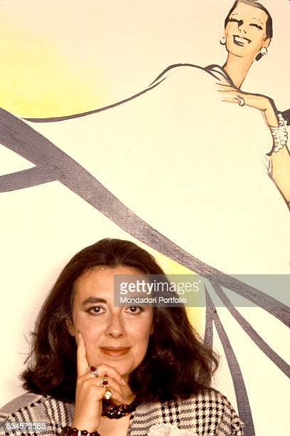 Stylist Laura Biagiotti in front of a sketch of a dress on the wall 80's