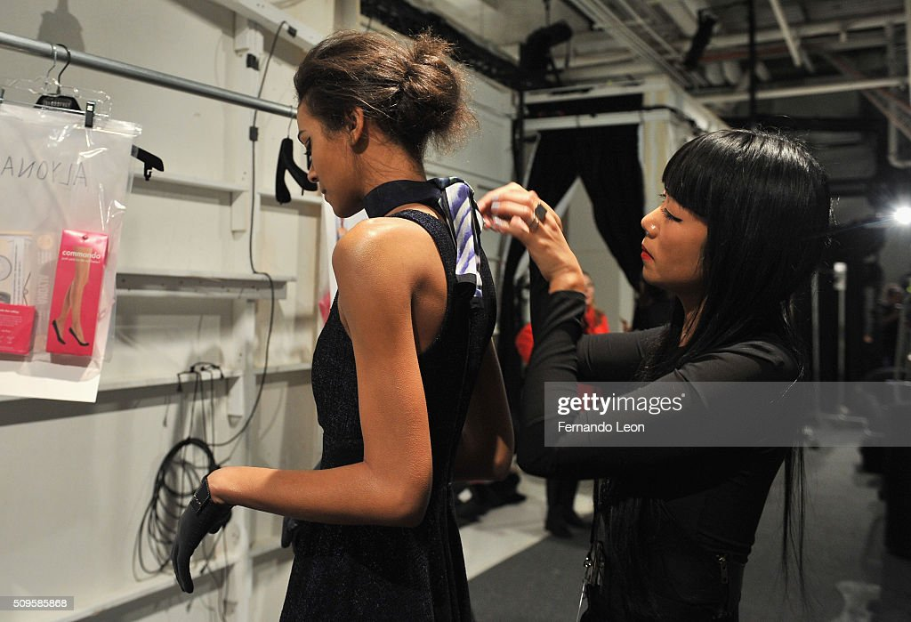 Stylist, Lisa Nguyen, prepares a model at Jay Godfrey Fall 2016 during New York Fashion Week: The Shows at The Space, Skylight at Clarkson Square on February 11, 2016 in New York City.