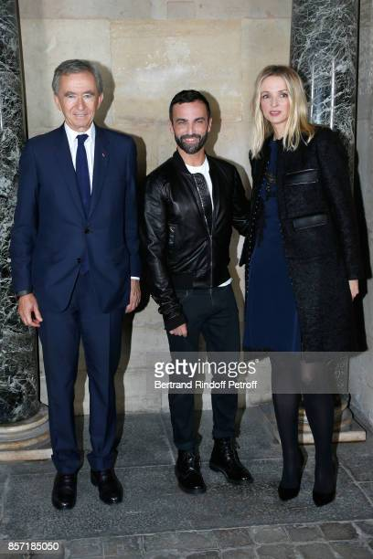 Stylist Nicolas Ghesquiere standing between Owner of LVMH Luxury Group Bernard Arnault and his daughter Louis Vuitton's executive vice president...