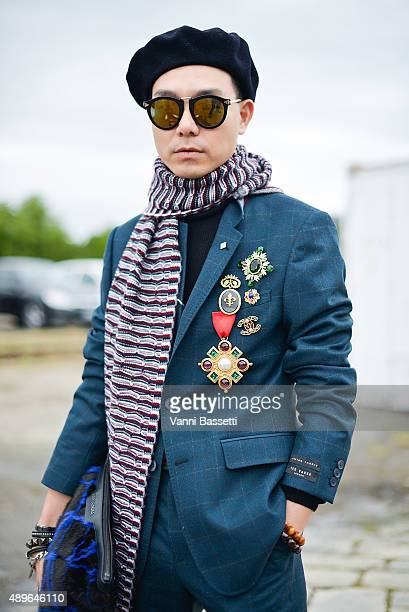 Stylist Ricky Kwok poses wearing a Ted Baker suit Carven scarf and Jimmy Choo bag before the Gucci show during the Milan Fashion Week Spring/Summer...