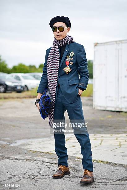Stylist Ricky Kwok poses wearing a Ted Baker suit Carven scarf Jimmy Choo bag and Tod's shoes before the Gucci show during the Milan Fashion Week...