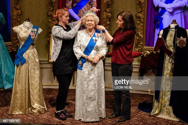 Stylists Jane Anderson and Luisa Compabassi pose with the restyled wax figure of Britain's Queen Elizabeth II during a photocall at Madame Tussauds...