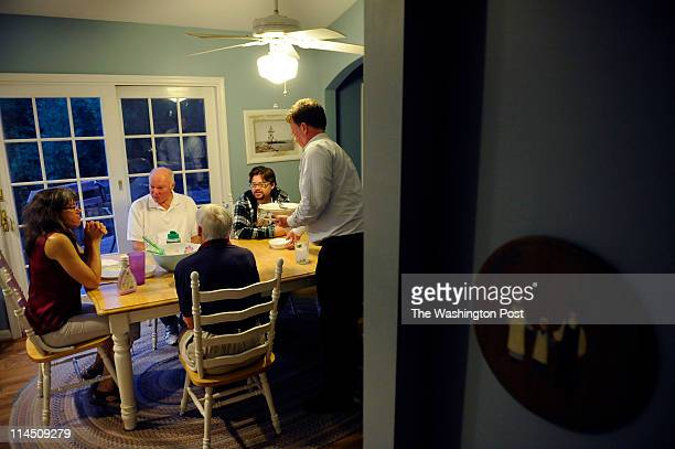 Su Meck far left sits at the dinner table after finishing eating with father Bob Miller left center mother Janet Miller center son Benjamin Meck and...