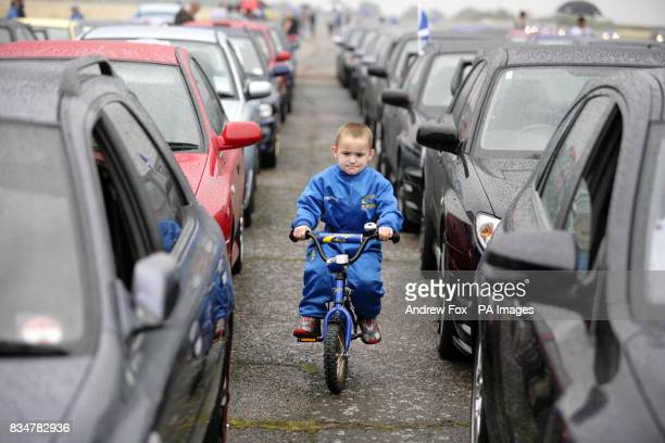 Subaru fan James Pemberton from Birmingham rides his Subaru bicycle through rows of Subaru cars wearing his rally driver's suit An estimated 1300...
