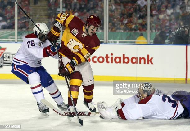 K Subban and Carey Price of the Montreal Canadiens defend the net against Curtis Glencross of the Calgary Flames during the 2011 NHL Heritage Classic...