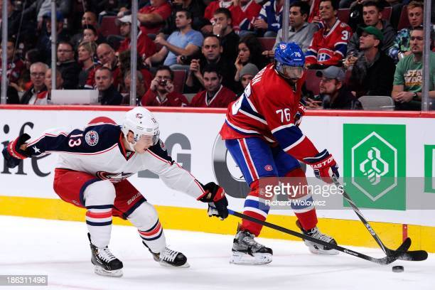 K Subban of the Montreal Canadiens clears the puck in front of Cam Atkinson of the Columbus Blue Jackets during the NHL game at the Bell Centre on...