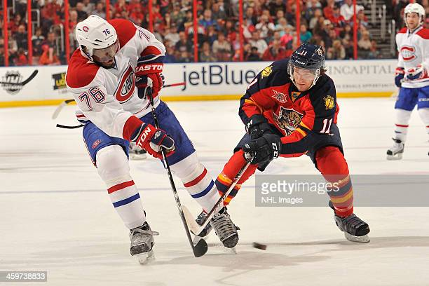 K Subban of the Montreal Canadiens crosses sticks with Jonathan Huberdeau of the Florida Panthers at the BBT Center on December 29 2013 in Sunrise...