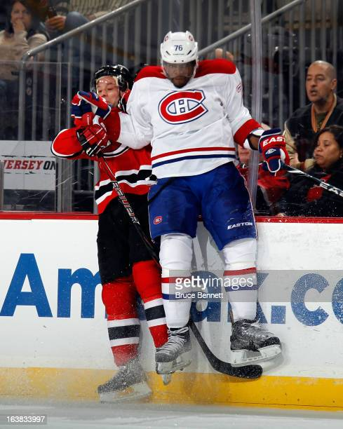 K Subban of the Montreal Canadiens hits Andy Greene of the New Jersey Devils during the second period at the Prudential Center on March 16 2013 in...