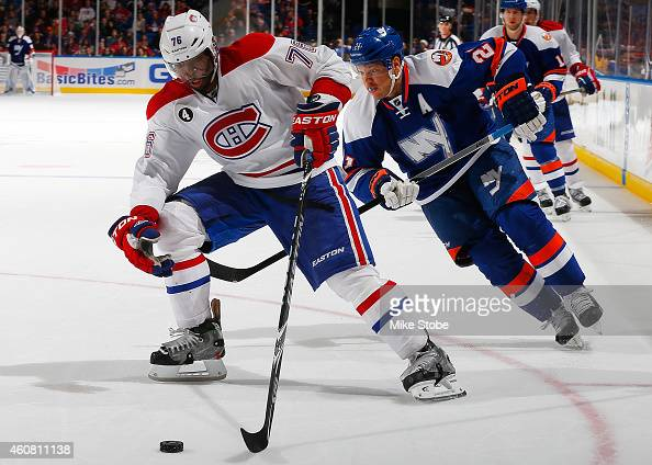 K Subban of the Montreal Canadiens is pursued by Kyle Okposo of the New York Islanders at Nassau Veterans Memorial Coliseum on December 23 2014 in...