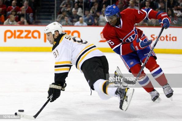 K Subban of the Montreal Canadiens trips Marc Savard of the Boston Bruins during the NHL game at the Bell Centre on December 16 2010 in Montreal...