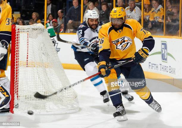 K Subban of the Nashville Predators clears the puck against Dustin Byfuglien of the Winnipeg Jets during an NHL game at Bridgestone Arena on March 13...