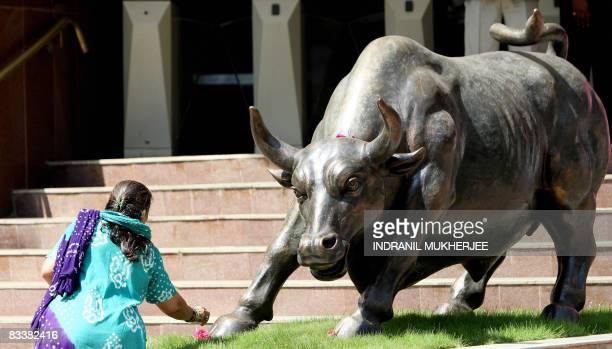 A subbroker makes flower offerings before the statue of a bull outside the Bombay Stock Exchange ahead of trading in Mumbai on October 22 2008 Indian...