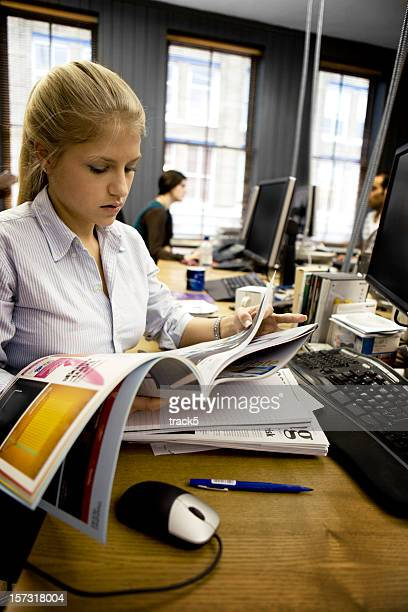 Sub-editor of a publishing team browsing through a magazine