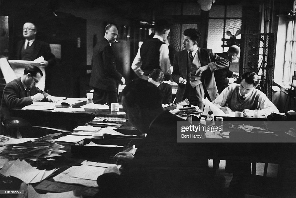 Sub-editors work on material from reporters and from a tape machine on a Saturday afternoon in the newsroom at the offices of the News of The World, April 1953. In the foreground (seated) is Sports Editor George Forrest, who is working with the sports subs to deal with the rush of Saturday's sports results. Original Publication : Picture Post - 6488 - The News of The World - pub. 18th April 1953.