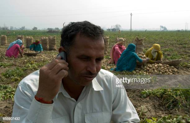 Subhash farm owner talking on mobile phone in Bazida Zattan Villagephotographed on February 24 2010 in Karnal India