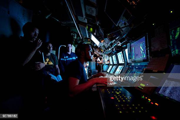 A submariner listens to a sonar in the French SNA class submarine 'Casabianca' on October 20 off Toulon southern France during a training session Un...