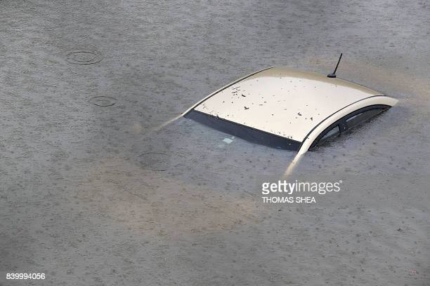 TOPSHOT A submerged car is seen on Interstate 610 North on August 27 2017 in Houston as the city battles with tropical storm Harvey and resulting...