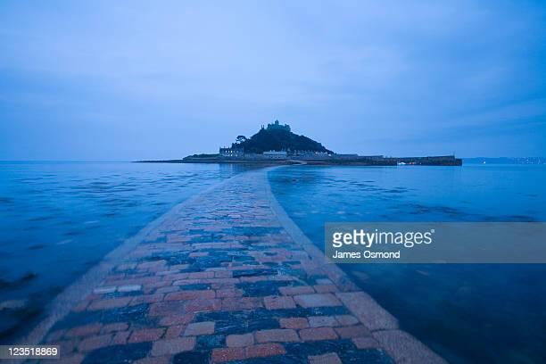 Submerged causeway leading St. Michael's Mount at dusk on the Cornish coast