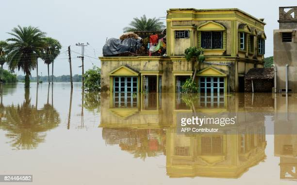 A submerged home is surrounded by flood waters in the Amta area of Howrah district around 55km west of Kolkata on July 30 2017 Major monsoon flooding...