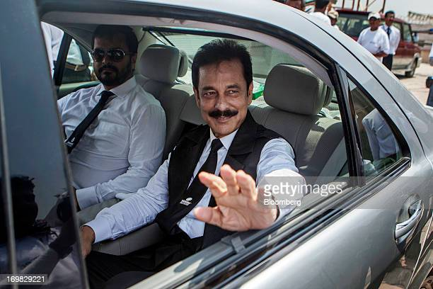 Subrata Roy chairman of Sahara Group center waves from a vehicle as he leaves a company event in Lucknow India on Monday May 6 2013 Roy's closely...