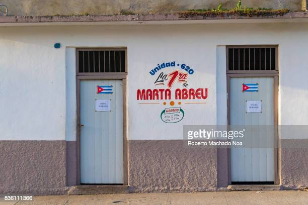 Subsidized rationed food store Building exterior with wall between two identical white doors with signs and Cuban flags